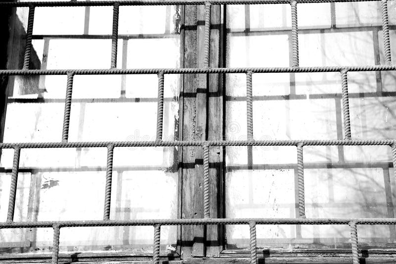 Old window painted white paint behind a rusty bars, black and white. Old window painted white paint behind a rusty bars closeup, black and white stock images