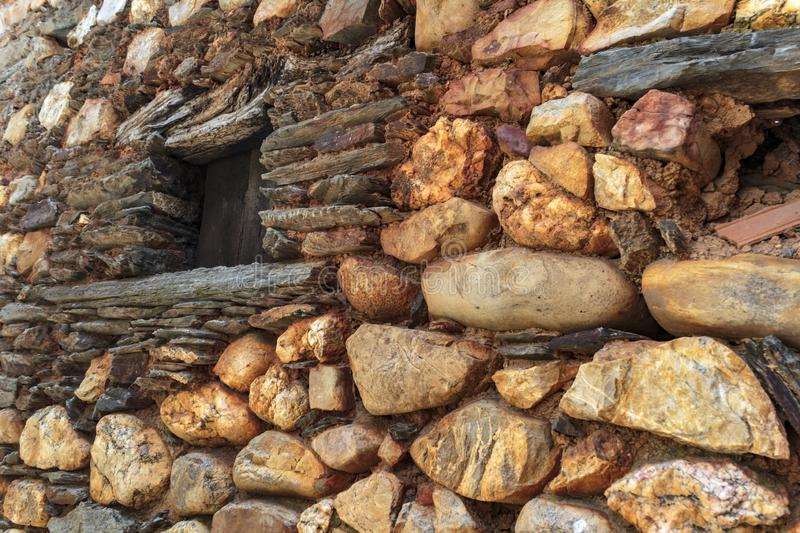 Old window on schist facades dotted with round stones from the river.  stock photography