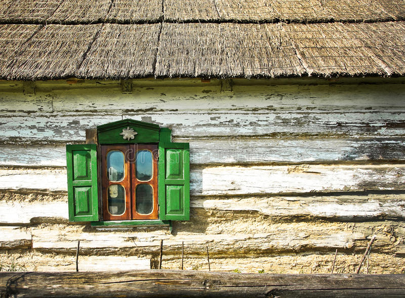 Old window with shutters. The open window with shutters on the facade of an old wooden farmhouse. Country log house with a reed roof - traditional Ukrainian stock photography