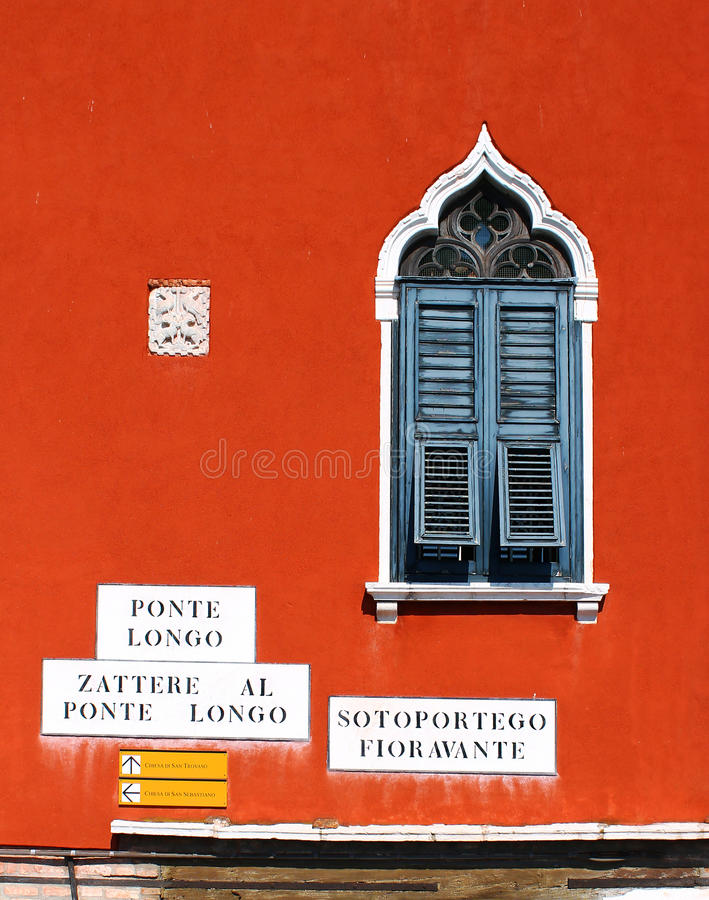 Old window with shutters on red-orange wall from Venice. Photo of an old window, shutters, street signs and old architectural details from Venice, Italy stock image