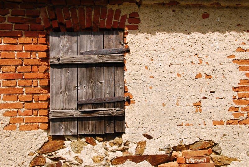 Old window shutters. Old wooden window shutters in old brick building stock photo