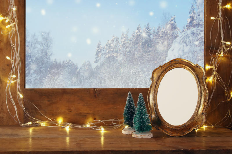 Old window sill with christmas lights and empty vintage frame stock photo