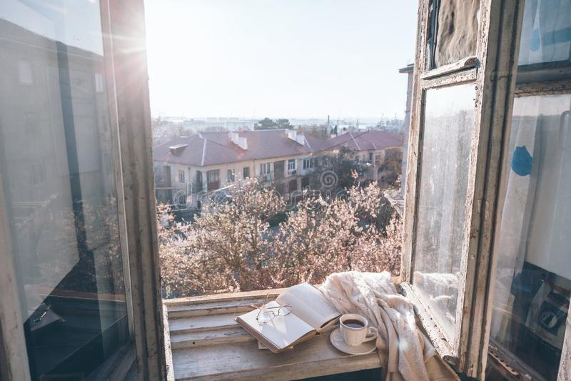 Old window with the view from inside. Into blooming tree. Opened book, cup of tea or coffee, glasses and knitted sweater on windowsill. Cozy spring weekend stock images