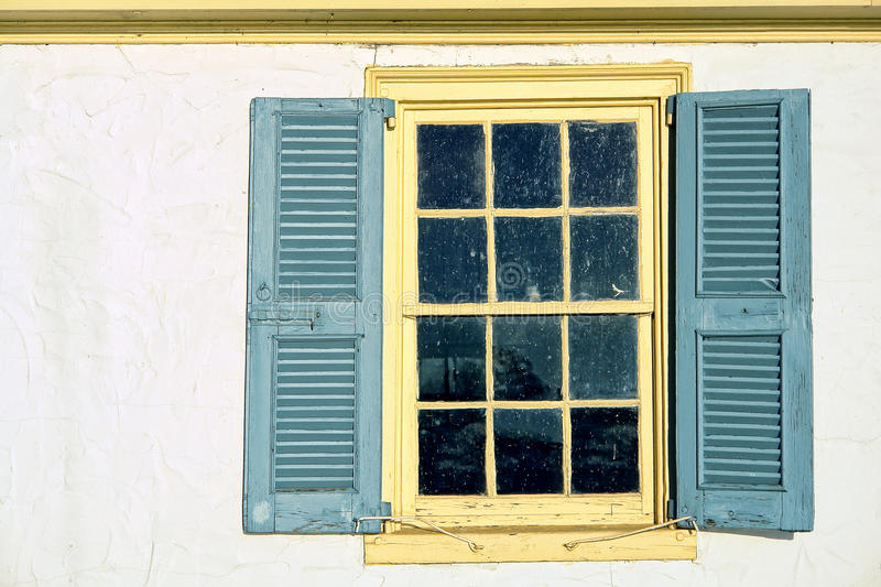 Old Window with Vintage Shutters on Historic Home. Old antique window with leaded glass panes and vintage wood shutters on a historic home colonial building stock photos