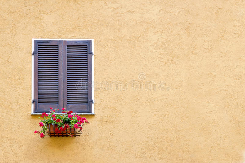 Old window with wooden shutters. On yellow stucco wall and copy space royalty free stock images