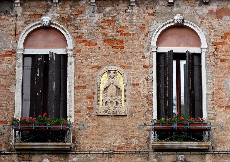 Old windows in Venice Italy with flowers and bricks stock images