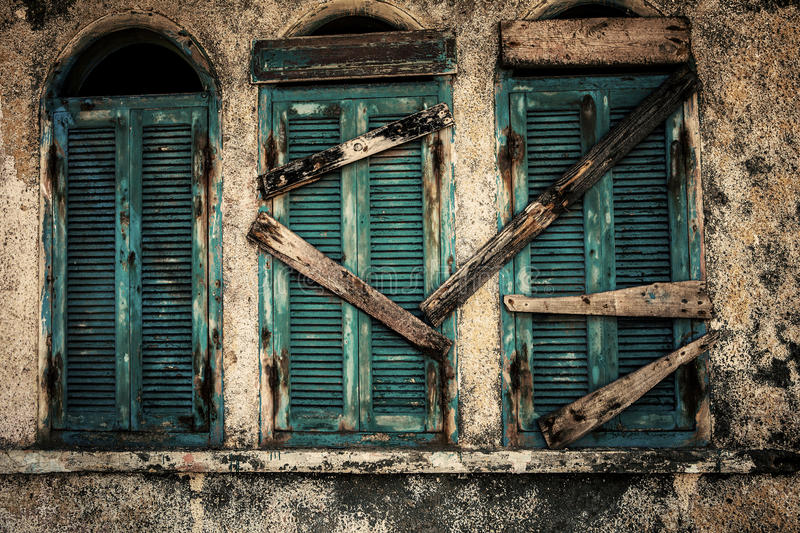 Old windows. Old vintage windows in green color closed by a wooden board royalty free stock photo