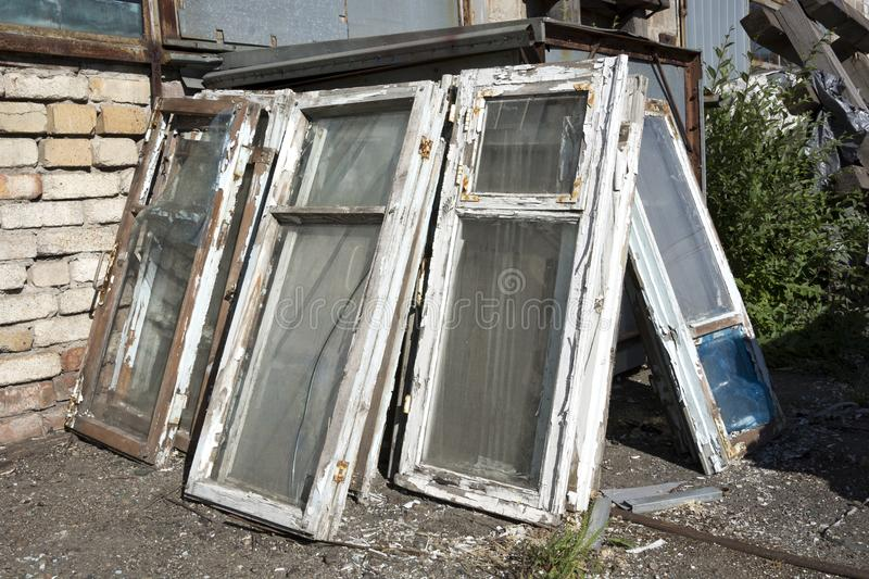 The old windows in a wooden frame with shabby white paint and broken glass lie in a heap in the dump royalty free stock photo