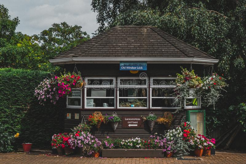 Old Windsor Lock Decorated with Colorful Plant Boxes. The Old Windsor Lock on the River Thames in England. Colorful flower boxes adorn the lock house, bringing stock photo