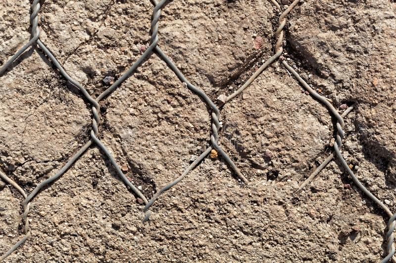 Old wire netting in concrete stock images