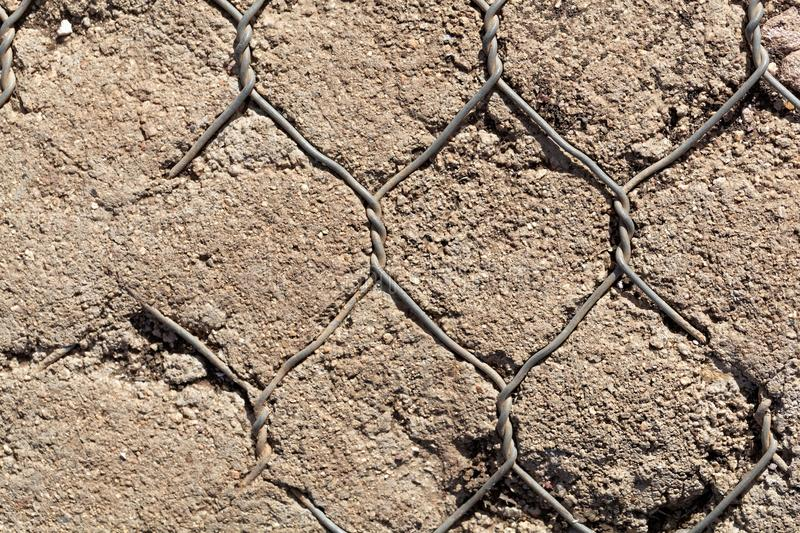 Old wire netting in concrete stock image