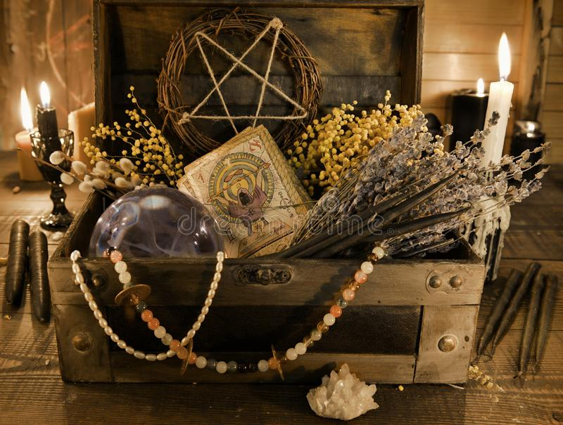 Old witch box with tarot cards, healing herbs and crystal ball on the table. Wicca, esoteric, divination and occult background with vintage magic objects for stock photos