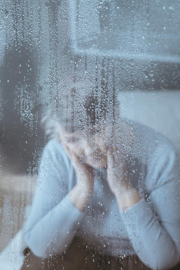 Old woman alone in house. Photo through window of worried old woman sitting alone in nursing house royalty free stock image