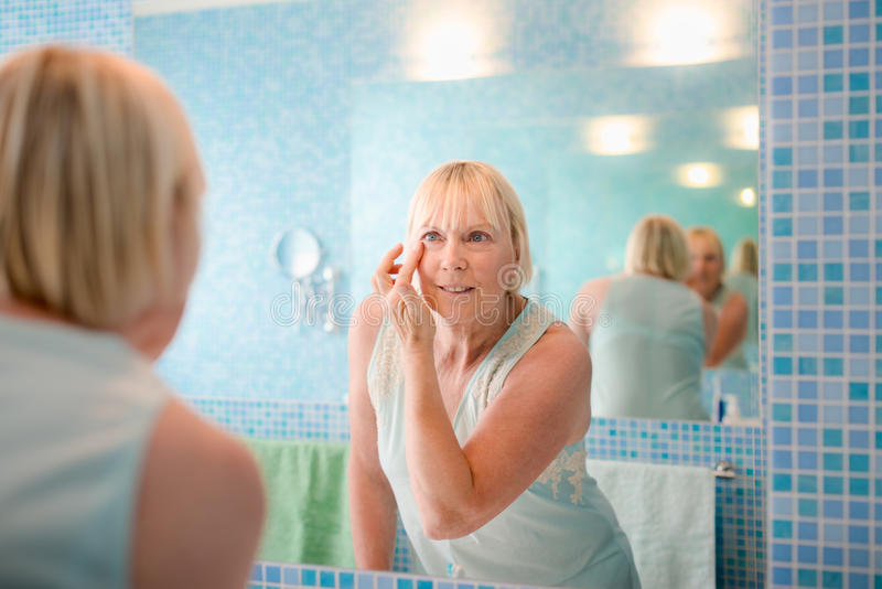 Old woman applying cream on face at home stock photos