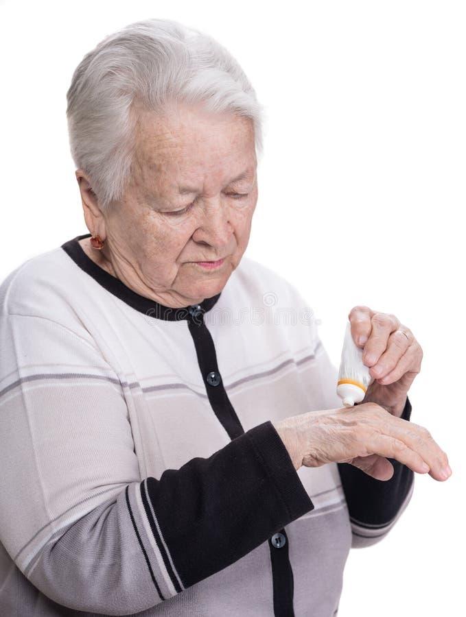 Old woman applying hand cream royalty free stock image