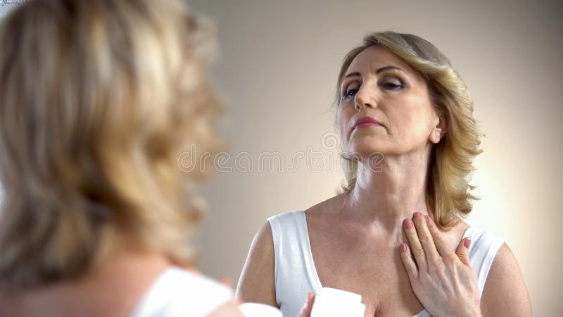 Old woman applying nourishing cream on neck and decollete zone, anti-age care stock photo