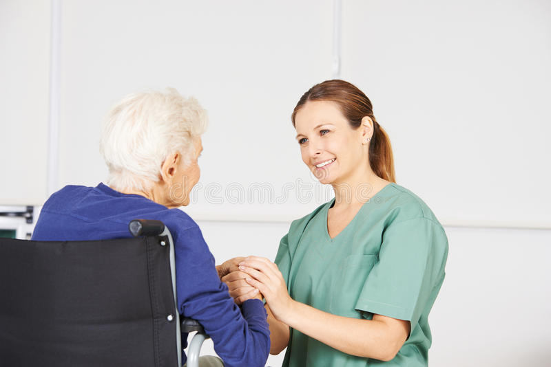 Old woman as patient with geriatric nurse. Old women in a wheelchair as patient with geriatric nurse in a nursing home stock images