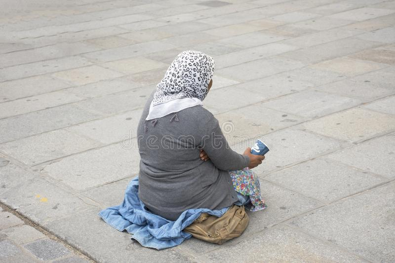 Old woman beggar sitting begging money from people. Old woman beggar sitting begging money from French people and foreigner travlers at walkway for go to visit royalty free stock images