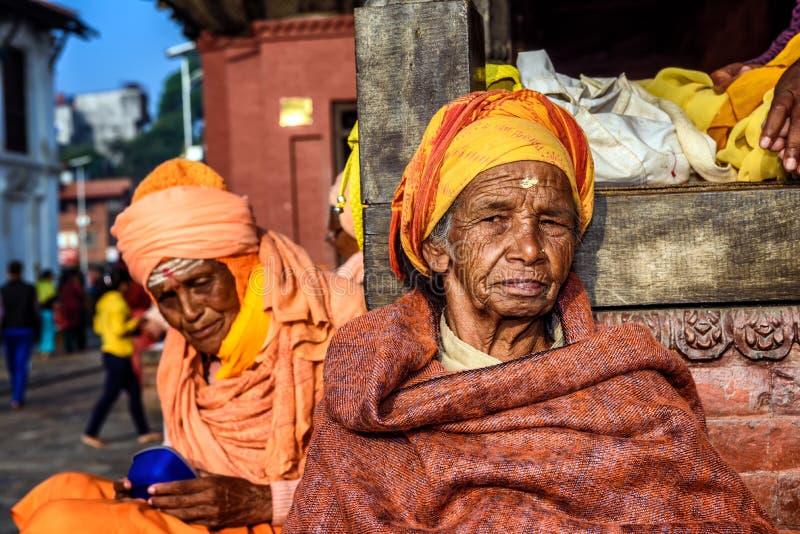 Old woman begging at Pashupatinath Temple complex in Kathmandu, Nepal. KATHMANDU, NEPAL - OCTOBER 20, 2015 : Old woman begging at Pashupatinath Temple complex in royalty free stock image