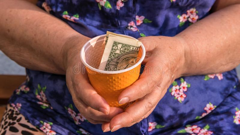 Old woman begs for alms. Closeup of money and coins in hand of poor woman stock photo