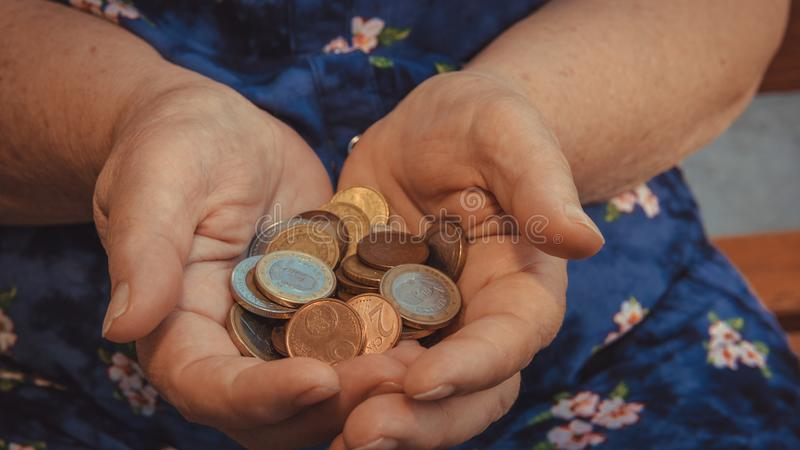 Old woman begs for alms. Closeup of money and coins in hand of poor woman stock images