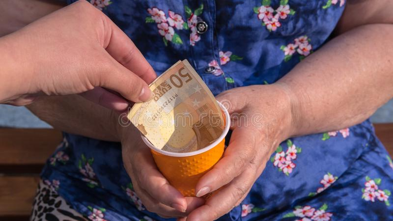 Old woman begs for alms. Closeup of money and coins in hand of poor woman royalty free stock photos