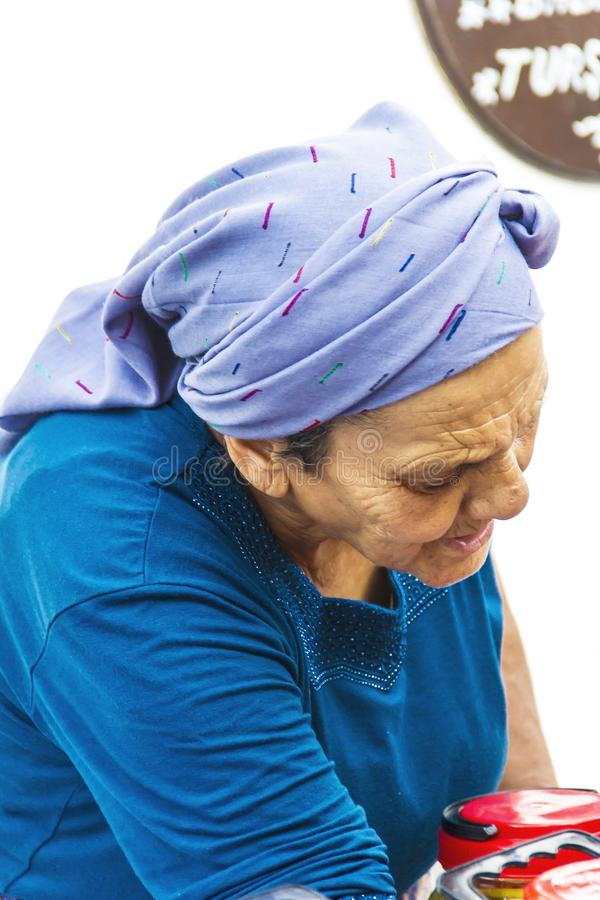 An Old Woman With Blue Dress And Scarf stock photography