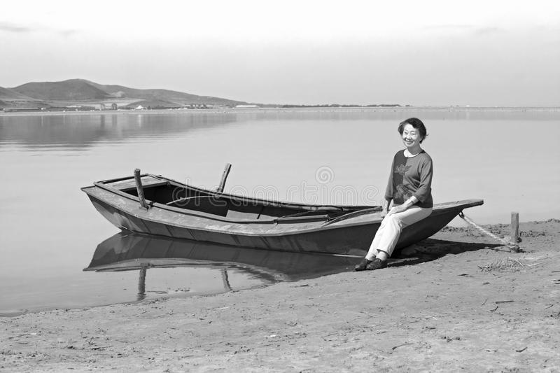 An old woman and boat stock photos
