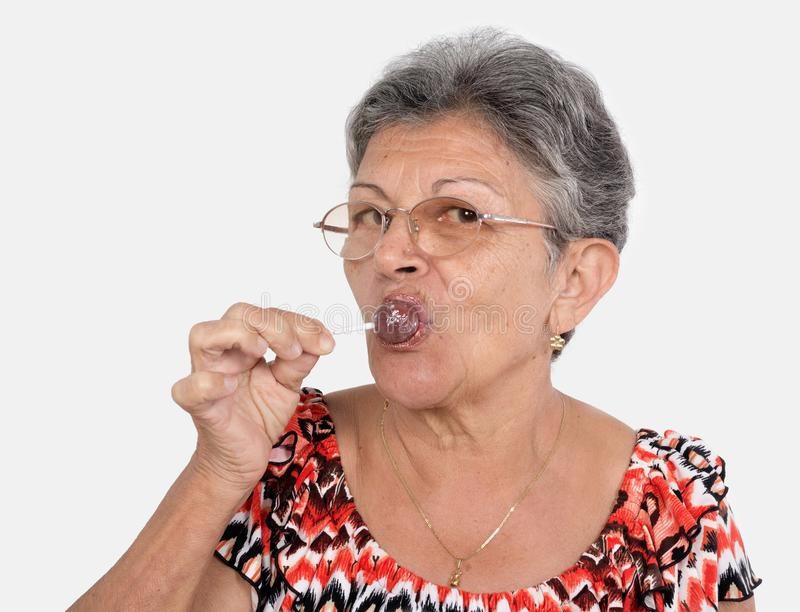 Old woman with a candy. An old woman wearing glasses with a candy in her mouse royalty free stock photography