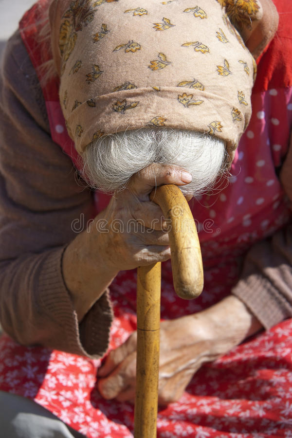 Old woman with a cane. Old peasant woman sitting leaning on a walking stick stock photography