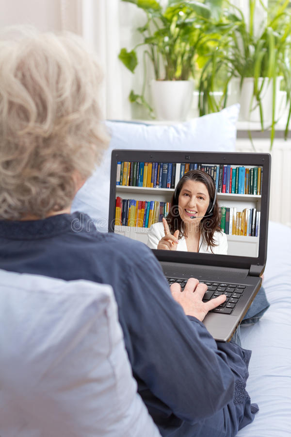 Old woman computer video lesson royalty free stock image