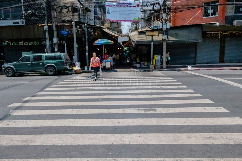 An old woman is crossing the street alone without traffic in Bangkok; Thailand April 14, 2018 stock image