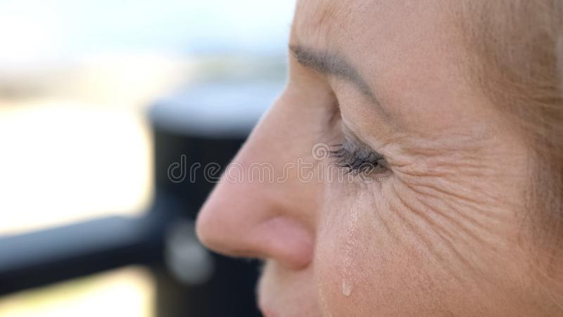 Old woman crying, relationship difficulties, pain of betrayal, domestic violence. Stock photo stock image