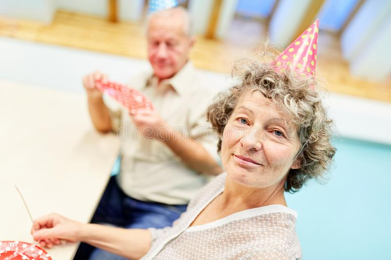 Old woman with dementia is celebrating at a party stock photography