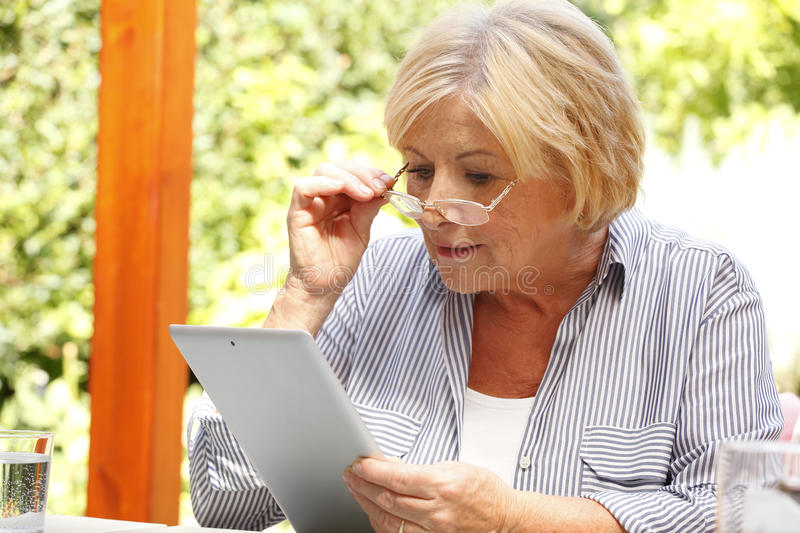Old woman with digital tablet royalty free stock photo
