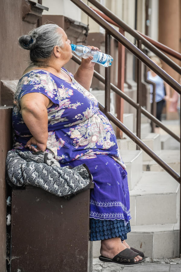 Old woman drinking water. While sitting in front of an old tenement house in Bydgoszcz, Poland stock photography