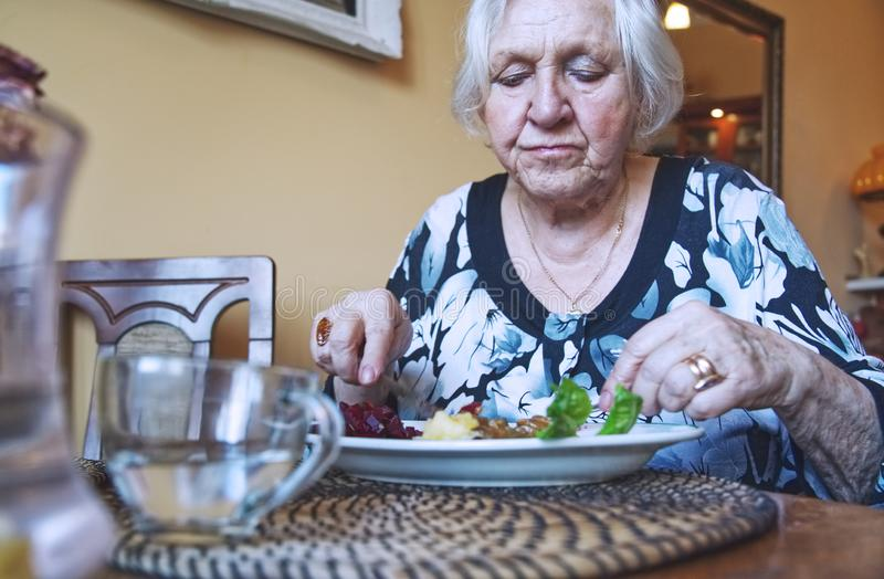 Old woman eating dinner alone. stock photos