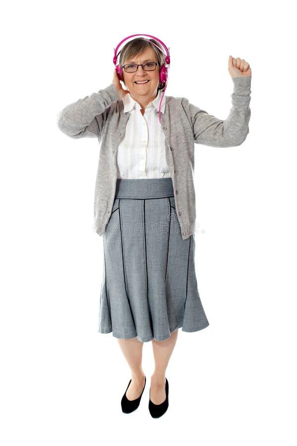 Old Woman Enjoying Music Stock Photo