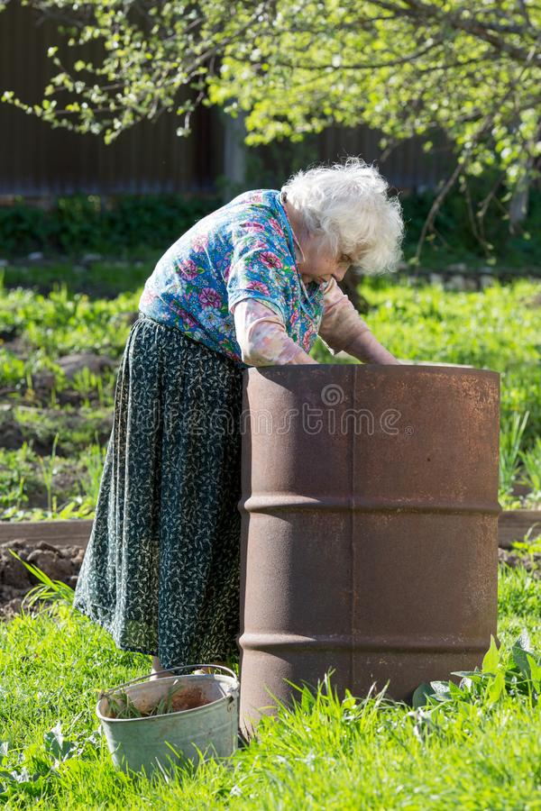 Old woman in the garden at an iron barrel royalty free stock photo