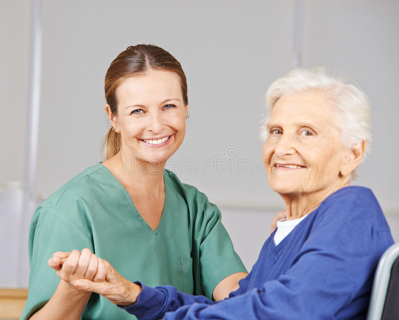 Old woman with geriatric nurse in nursing home. Old smiling senior women with geriatric nurse in a nursing home royalty free stock photo