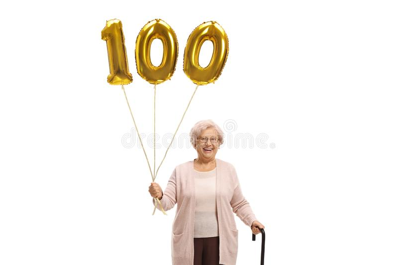 Old woman with a golden number hundred balloon and a walking cane. Isolated on white background stock photography