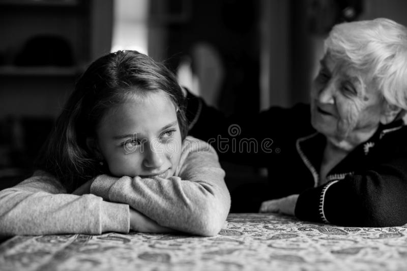 Old woman grandmother comforting a crying little girl granddaughter. Old women grandmother comforting a crying little cute girl granddaughter royalty free stock photography
