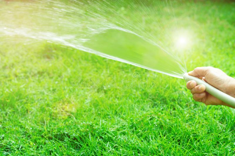 Old woman hand holding rubber water hose and using finger close end of rubber water hose to make water spray with sunlight royalty free stock image