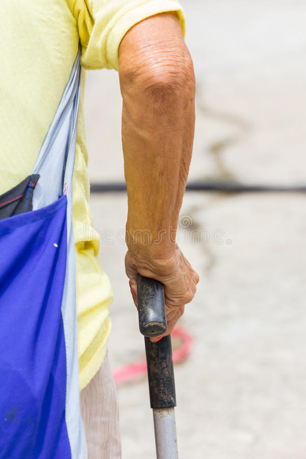 Old woman hand leans on walking stick, close-up stock images