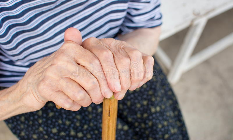 Old woman hands holding a walking cane. Outdoors stock photos