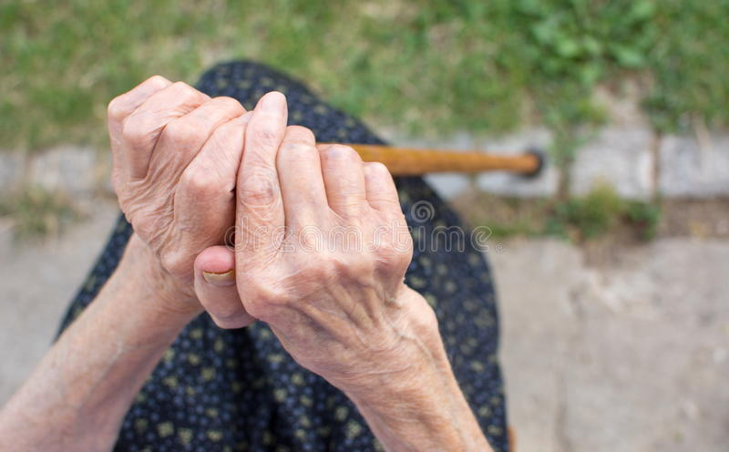 Old woman hands holding a walking cane. Outdoors royalty free stock photography