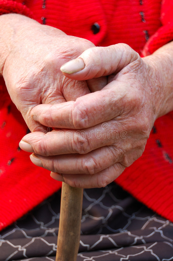 Old woman hands leans on walking stick stock photo