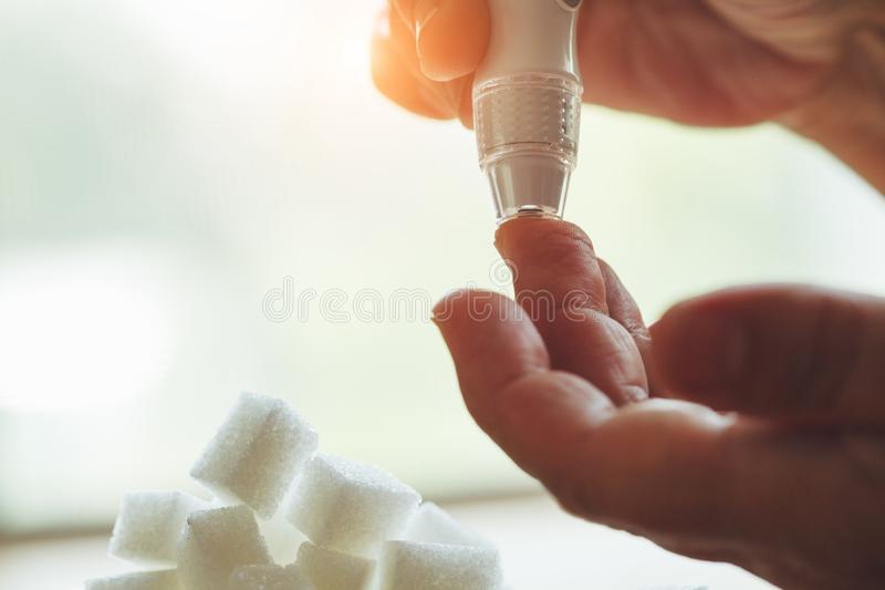 Old woman hands using lancet on finger to check blood sugar level, glucometer  and sugar cubes on wooden table close up, diabetes stock photo