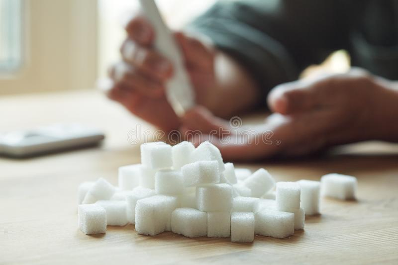 Old woman hands using lancet on finger to check blood sugar level, glucometer and sugar cubes on wooden table close up, diabetes stock photography