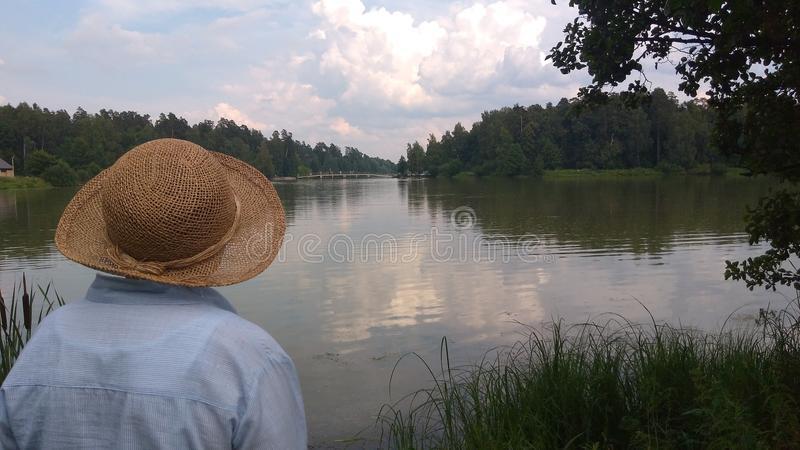Old woman in a hat looking at a lake. This is a photo of an old woman looking at the lake Loseney Ostrov located near Moscow royalty free stock photos